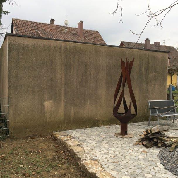 Eine Garagenrückwand vor der Sanierung mit starkem Pilz und Algenbefall