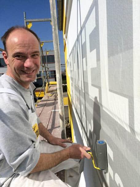 Steffen Hofele bringt sein Firmenlogo von Hofele Stuckateur und Maler aus Süssen mittels Schablone an.
